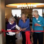Three of St. Andrew's first residents cut the ceremonial red ribbon.